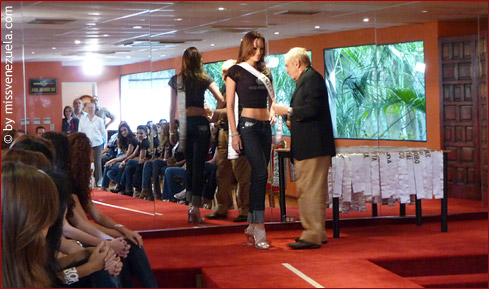 Osmel Sousa checking a candidate's sash and stance before walking the ramp.