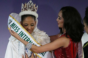 Miss International 2013 Bea Rose Santiago putting the sash on her successor, Valerie Hernandez Matias